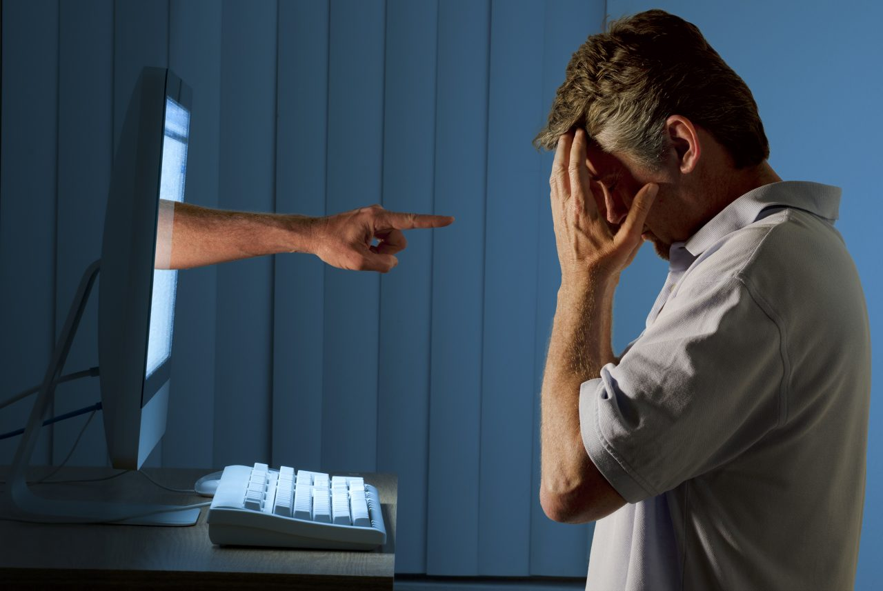 Severely distraught young man sitting in front of a computer with a judgmental hand pointing at him from within the computer monitor
