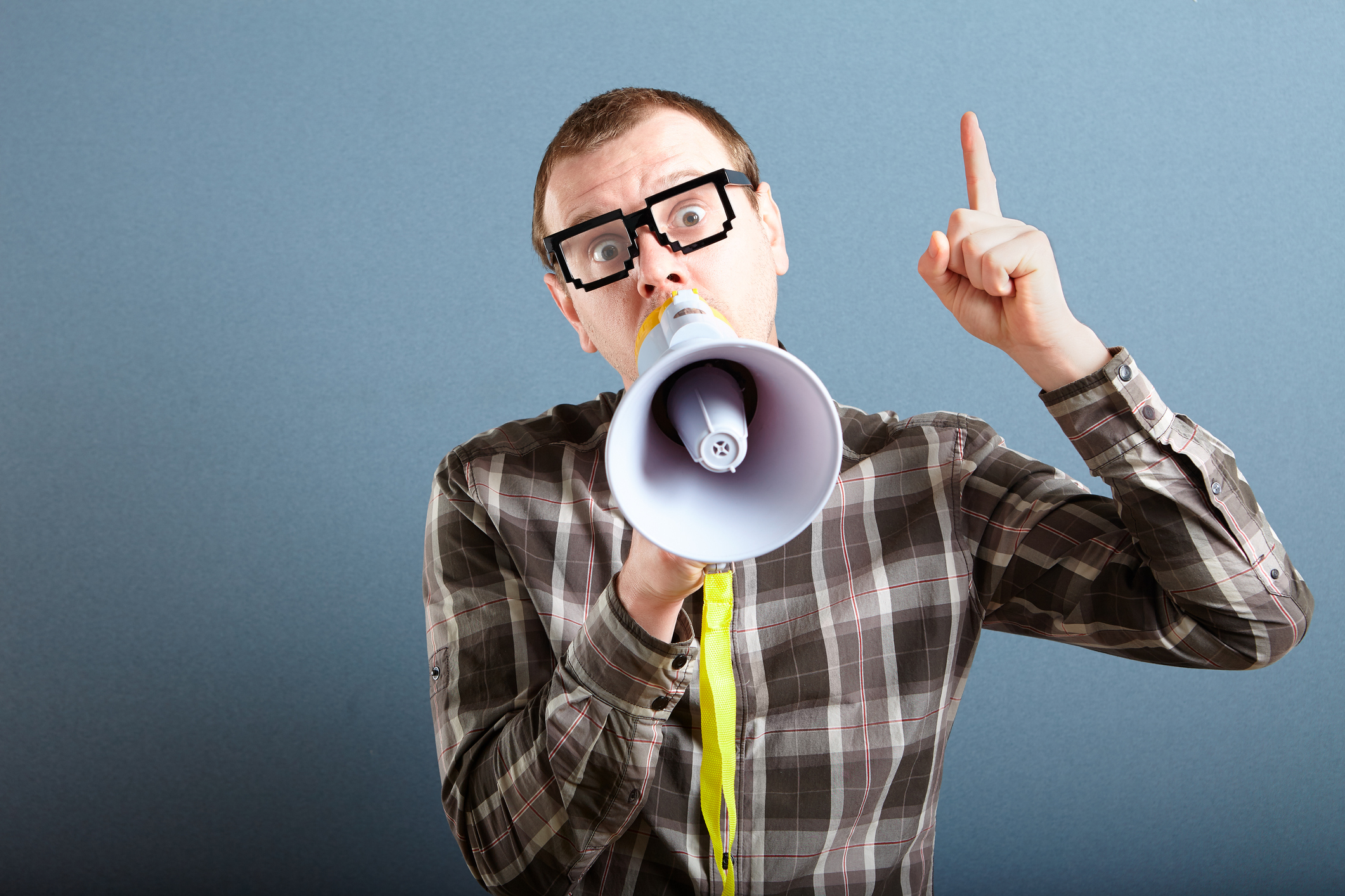Nerdy guy with glasses holding megaphone and screaming loud, and gesturing with index finger raised