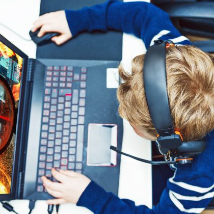 One boy sits in front of a computer. He holds on to a computer mouse and types on the keyboard. He looks at the computer screen and plays a game.