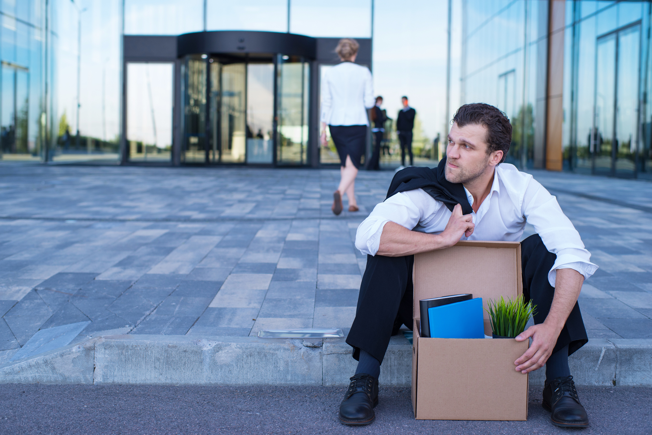 Fired business man sitting frustrated and upset on the street near office building with box of his belongings.