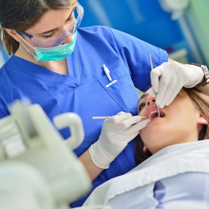 happy female dentist checking patient girl teeth up at dental clinic office
