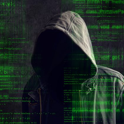 hacker in a hoodie with code