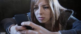 worried woman stares at phone