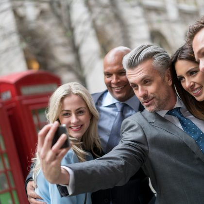 Group of business people taking a selfie outdoors with a smart phone