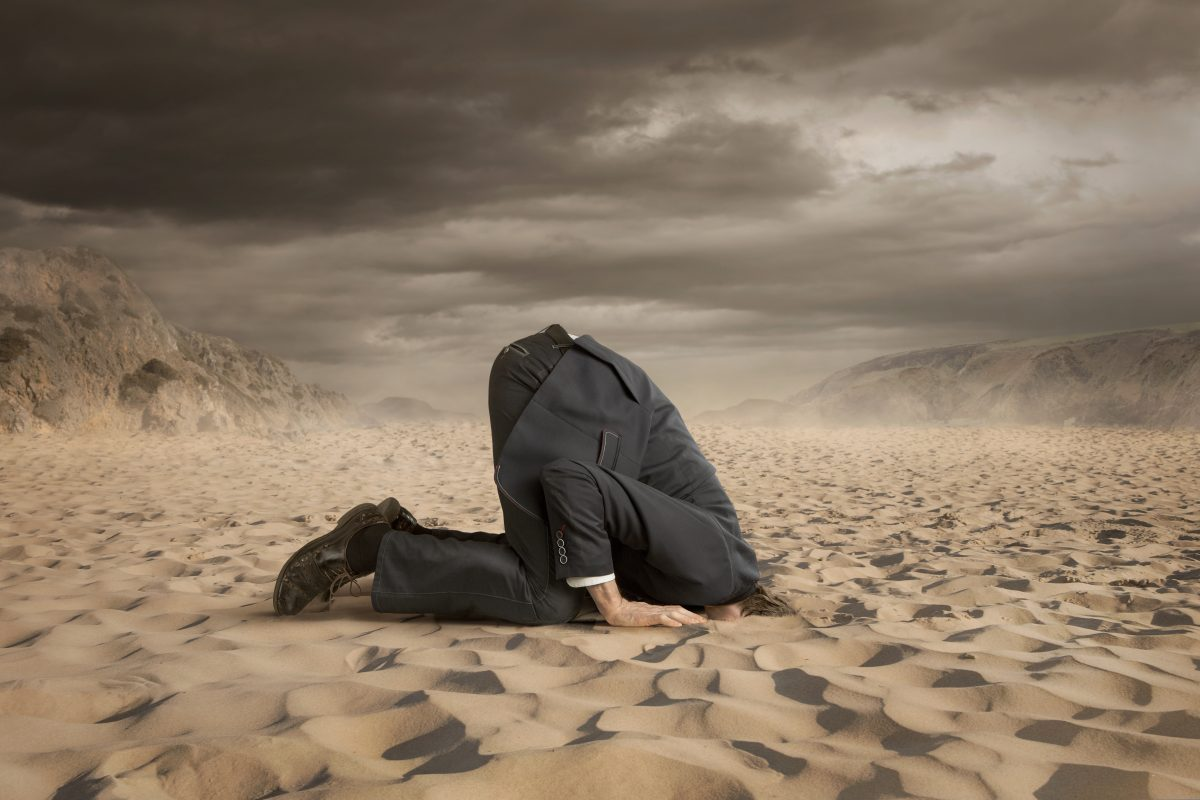 A businessman with his head in the sand like an ostrich