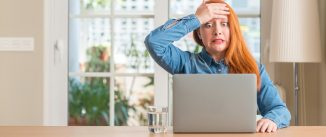 Redhead woman using computer laptop at home stressed with hand on head, shocked with shame and surprise face, angry and frustrated. Fear and upset for mistake.