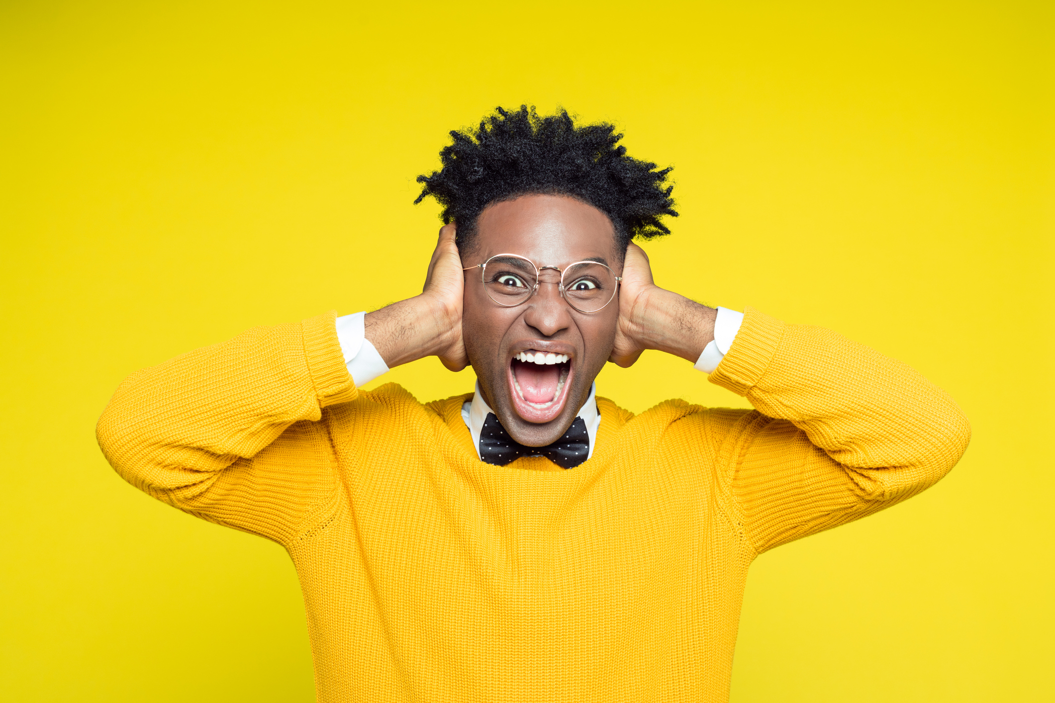 Portrait of angry nerdy young afro american man wearing yellow sweater and black bow tie shouting at the camera against yellow background.
