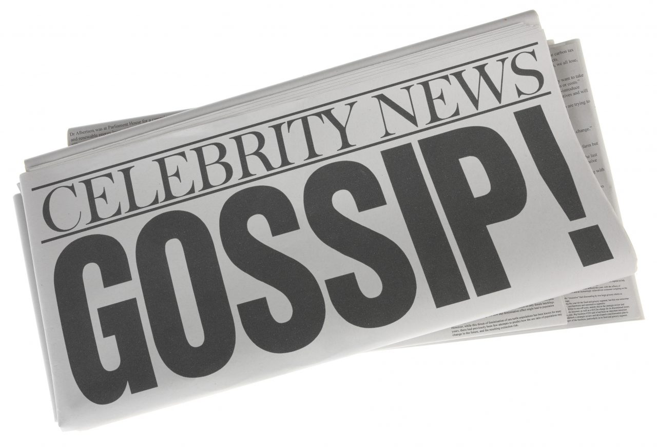 Gossip as a headline on a stack of folded newspapers isolated on white. Stock photo of a headline on a pile of newspapers on white background.