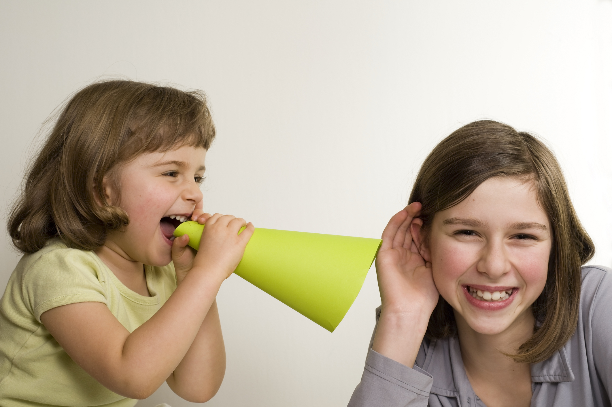 Girl shouting into a megaphone while another girl listens