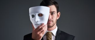 Studio portrait of a young businessman holding a mask in front of his face against a gray background