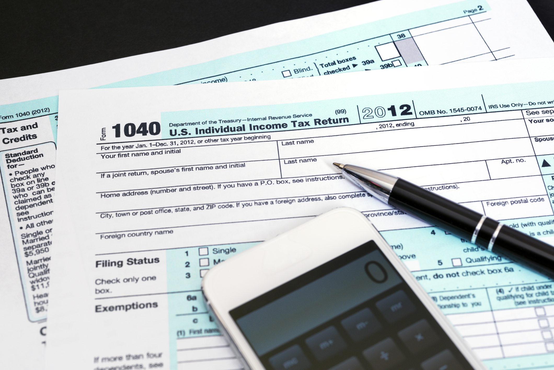 1040 tax forms with a phone and pen