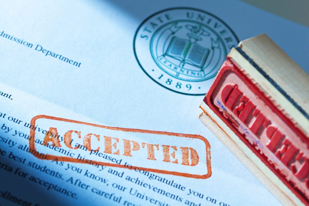 "An acceptance letter from a university application. An university application form and the letter of acceptance with a red rubber stamp of ""Accepted"" on a table top still life. Photographed close-up in horizontal format with selected focus on the rubber stamp impression."