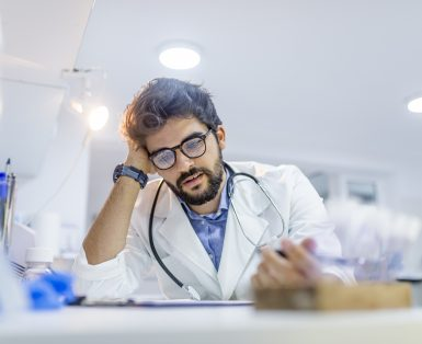Overworked doctor in his office. Mid adult doctor contemplating in his office. Worried and tired mid adult male doctor reading medical results on his clipboard.