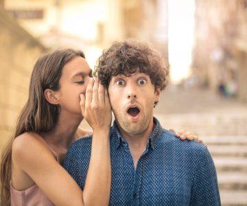 woman whispering secret to a man