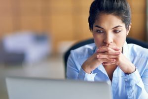worried woman looks at computer screen
