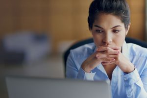 worried woman looks at her laptop