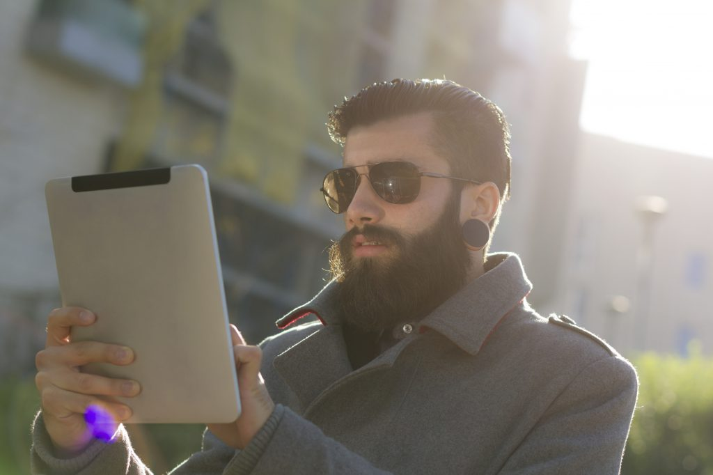 Young man (hispter style) with big earring and full beard, wearing sunglasses using a digital tablet outdoor. Sunlight and flares on picture.