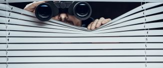 Man with binoculars looking through blinds.