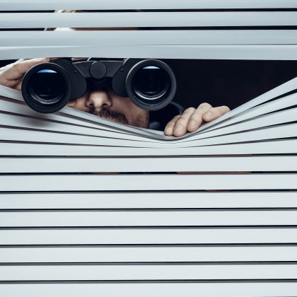 Man with binoculars looking through blinds.