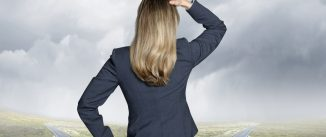 A businesswoman places her head on hand on her head as she stands at a fork in the road while looking ahead toward the horizon as the two roads disappear into the haze and mist.