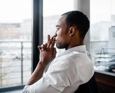 pensive black businessman looking out the window