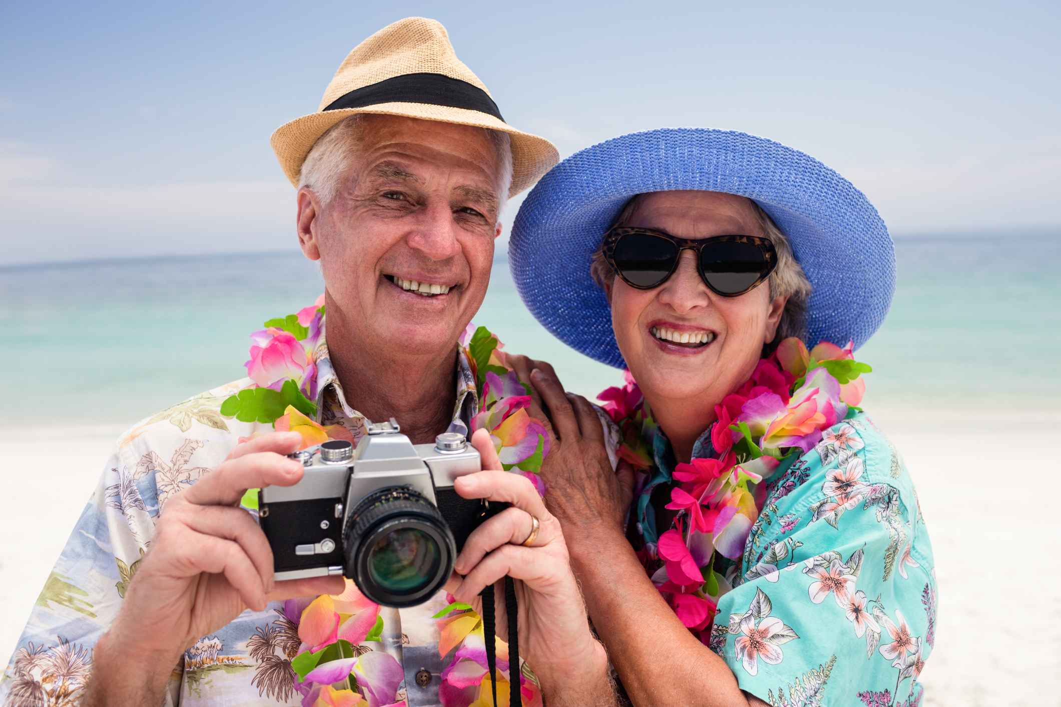 Senior couple clicking a photo with camera on the beach