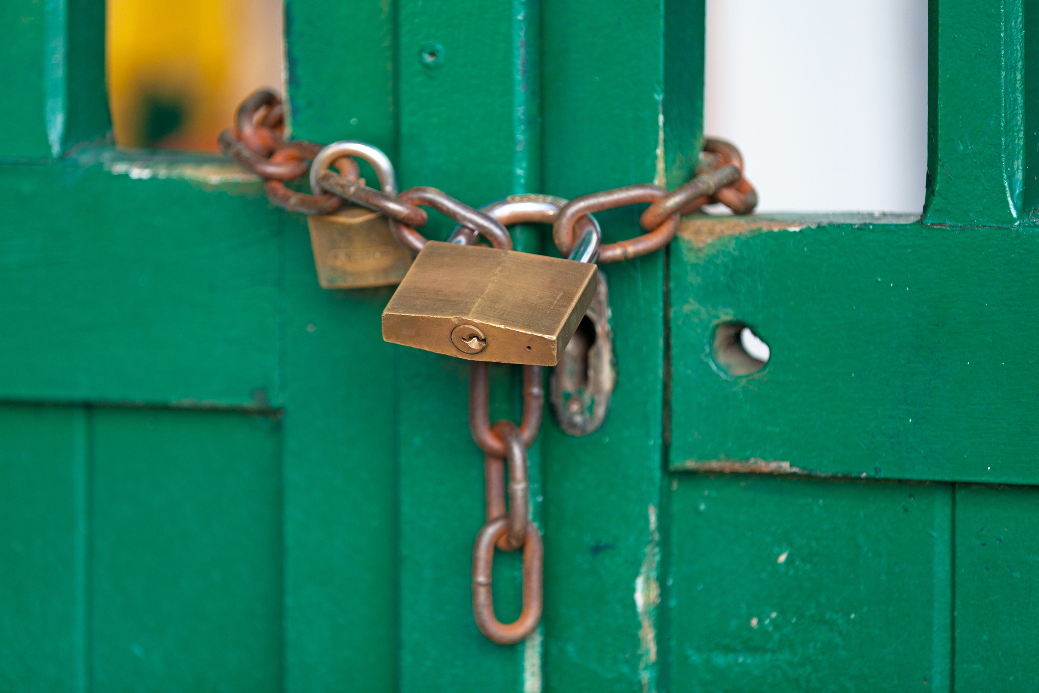 Close-up on a chain and a padlock closing a door.
