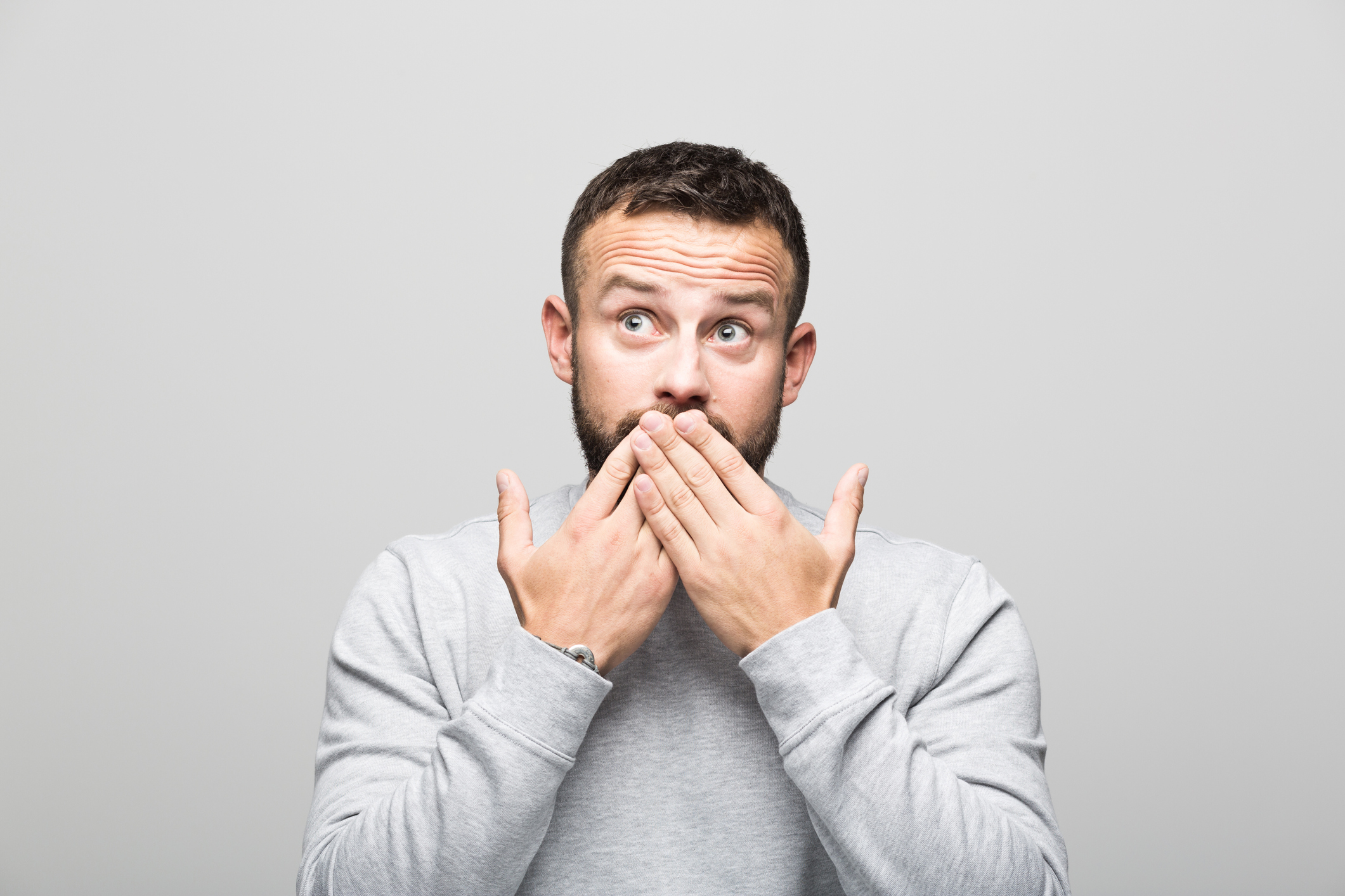 Portrait of shocked bearded young man looking up, grey background