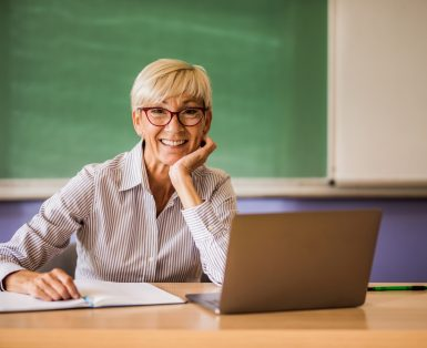 Happy mature teacher at the desk in the classroom.