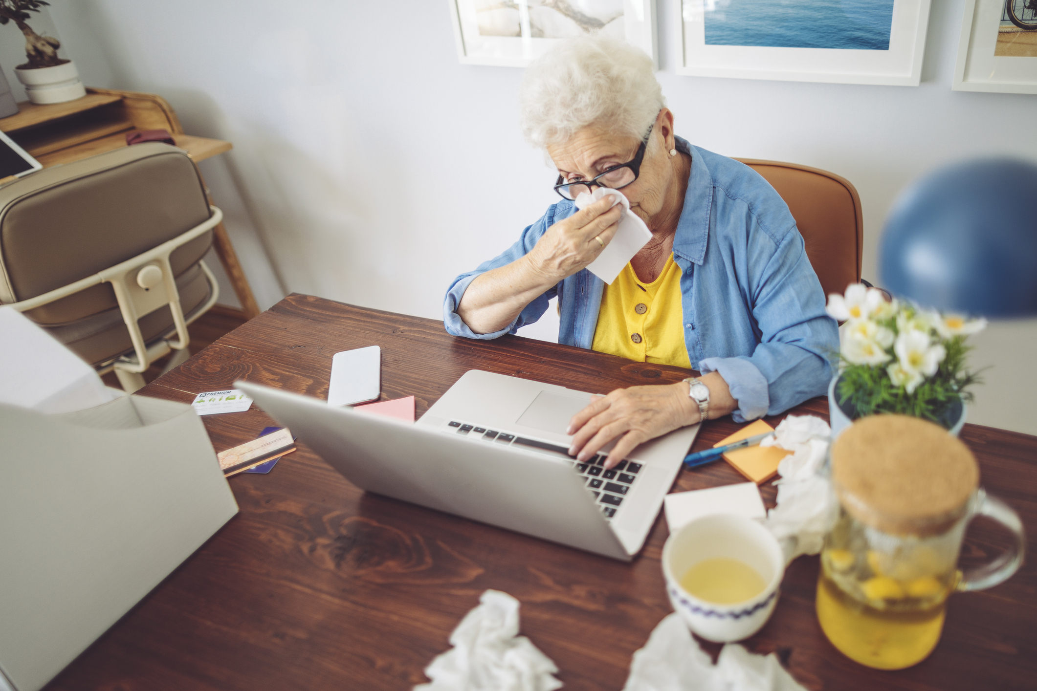 Senior woman at home on computer surrounded by used tissues.