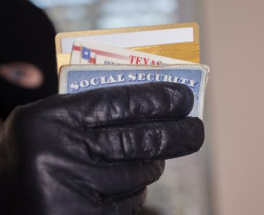 Masked theif steals a victim's identification cards.