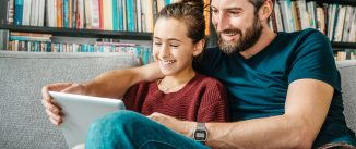 father and daughter having fun with digital tablet on couch