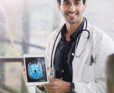 Male doctor showing a brain scan to colleagues.