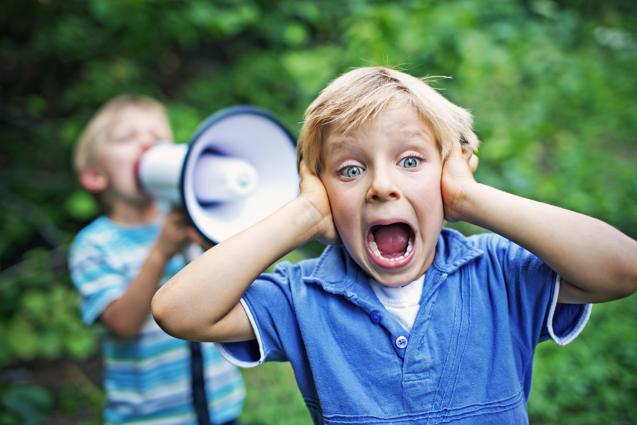 Little boy covering his ears while his brother is yelling on him with megaphone.