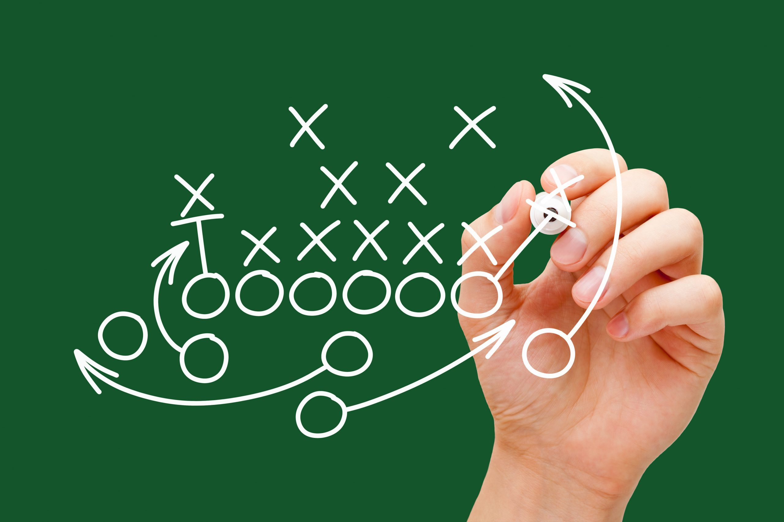 Coach drawing american football or rugby game playbook, strategy and tactics with white marker on green background.