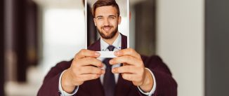 Smiling businessman showing photo on tablet