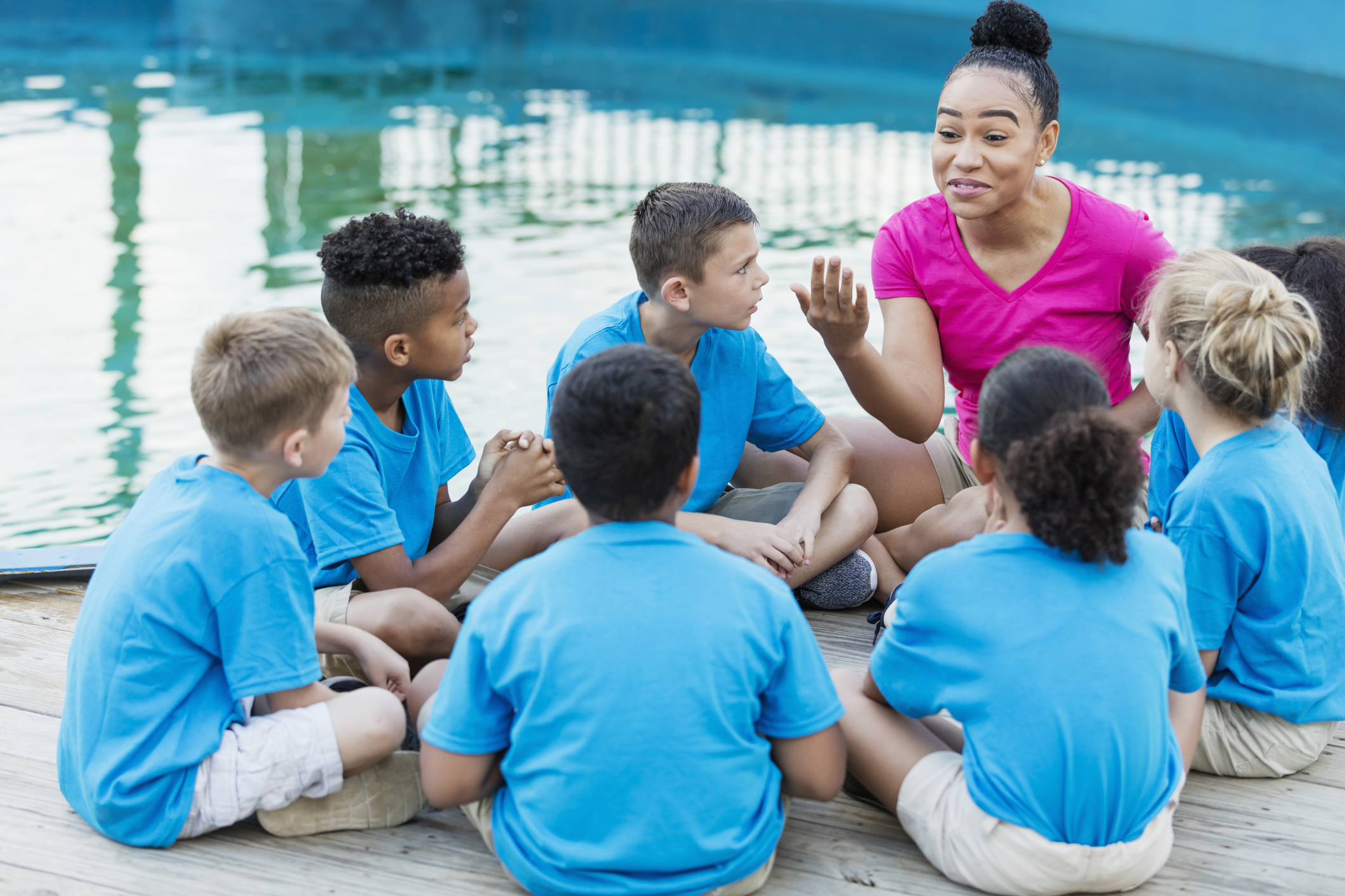A group of multi-ethnic children on a field trip to a marine park. They are sitting in a circle by a pool, listening intently to a young African-American woman telling a story.