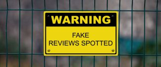 Yellow warning sign on a fence stating : Warning, Fake reviews spotted.