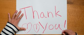 Child writes thank you on paper