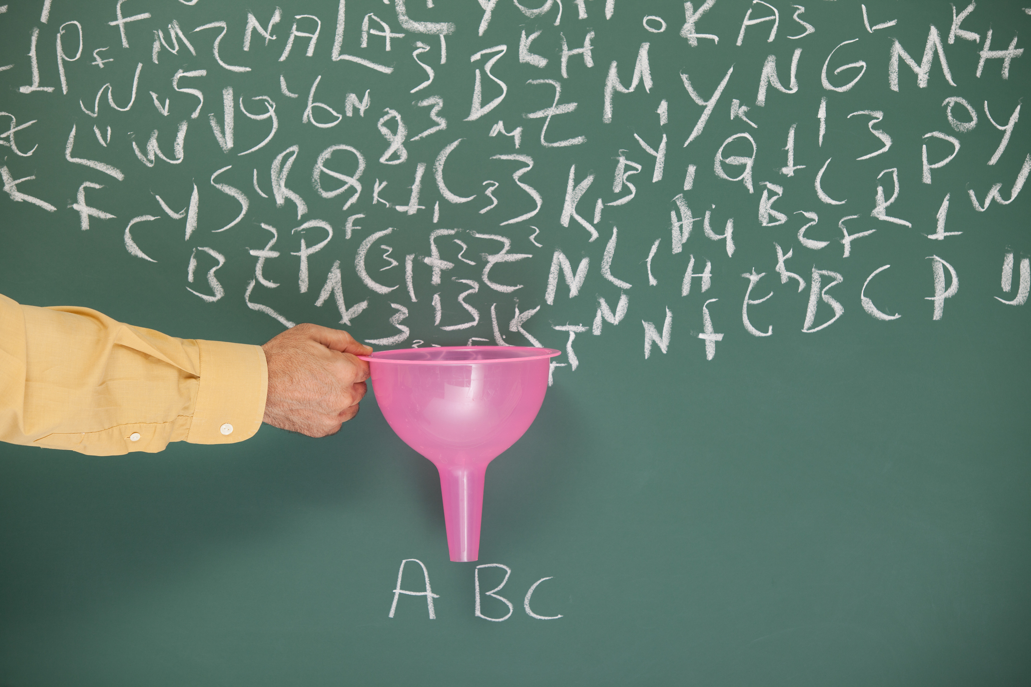 "A funnel in hand of man filtering letters written on blackboard by chalk.Search engine optimization -SEO- concept is aimed.The hand is on the left side of the horizontal frame.The funnel pink color is for having attention on filtering. The letters ""ABC"" is written under the funnel.Taken with a full frame DSLR camera."