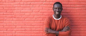 A young African man in a red sweater leaning against a red brick wall.