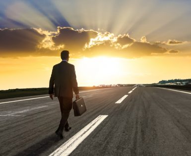 Entrepreneur, carrying a briefcase, walking on an empty highway at sunset.