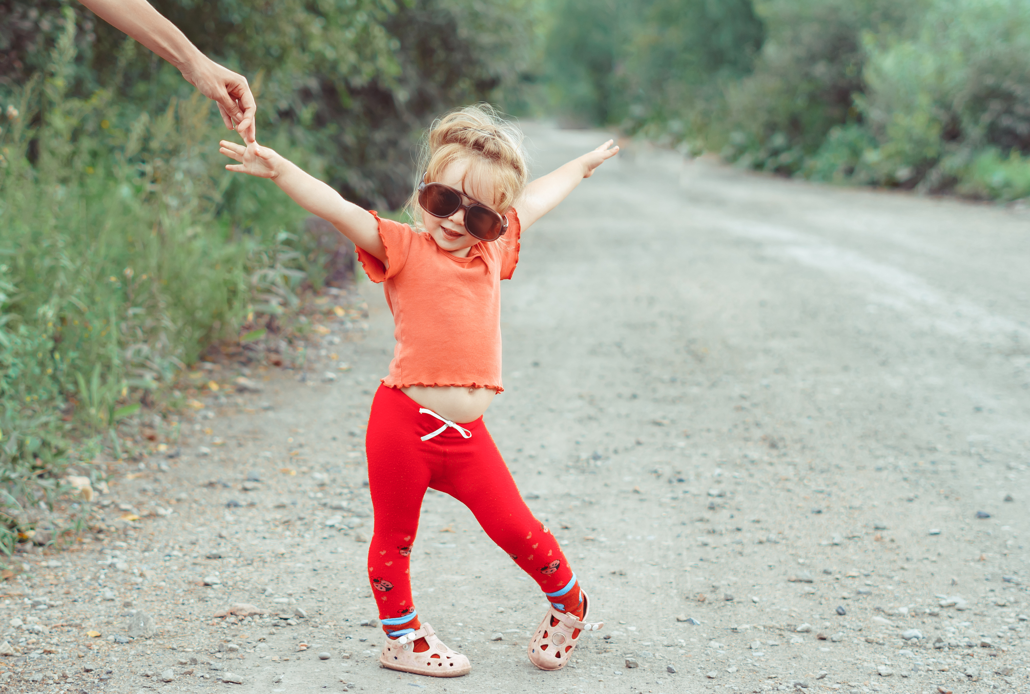 little girl dancing in glasses outdoors