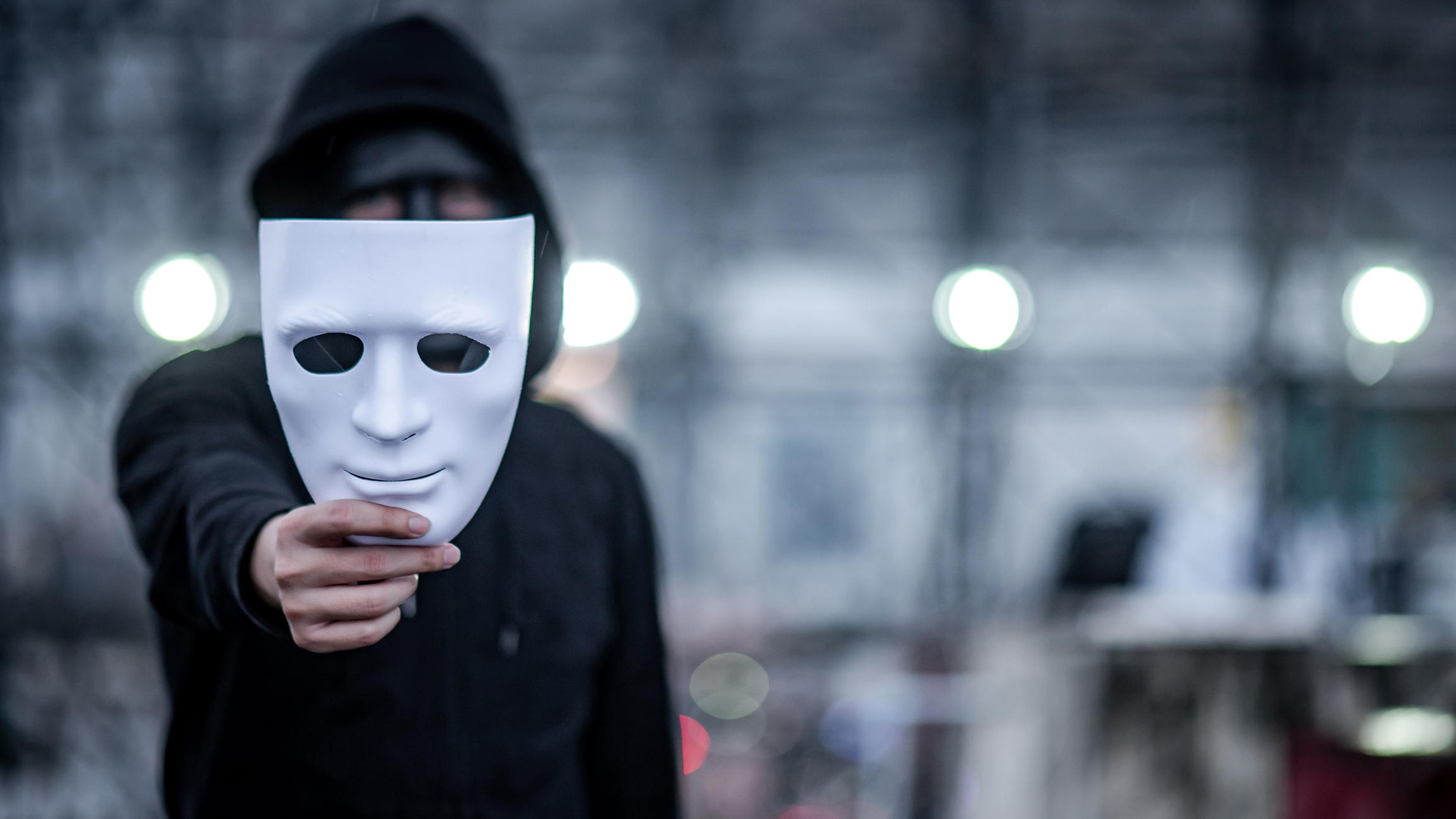Mystery hoodie man with black mask holding white mask in his hand.