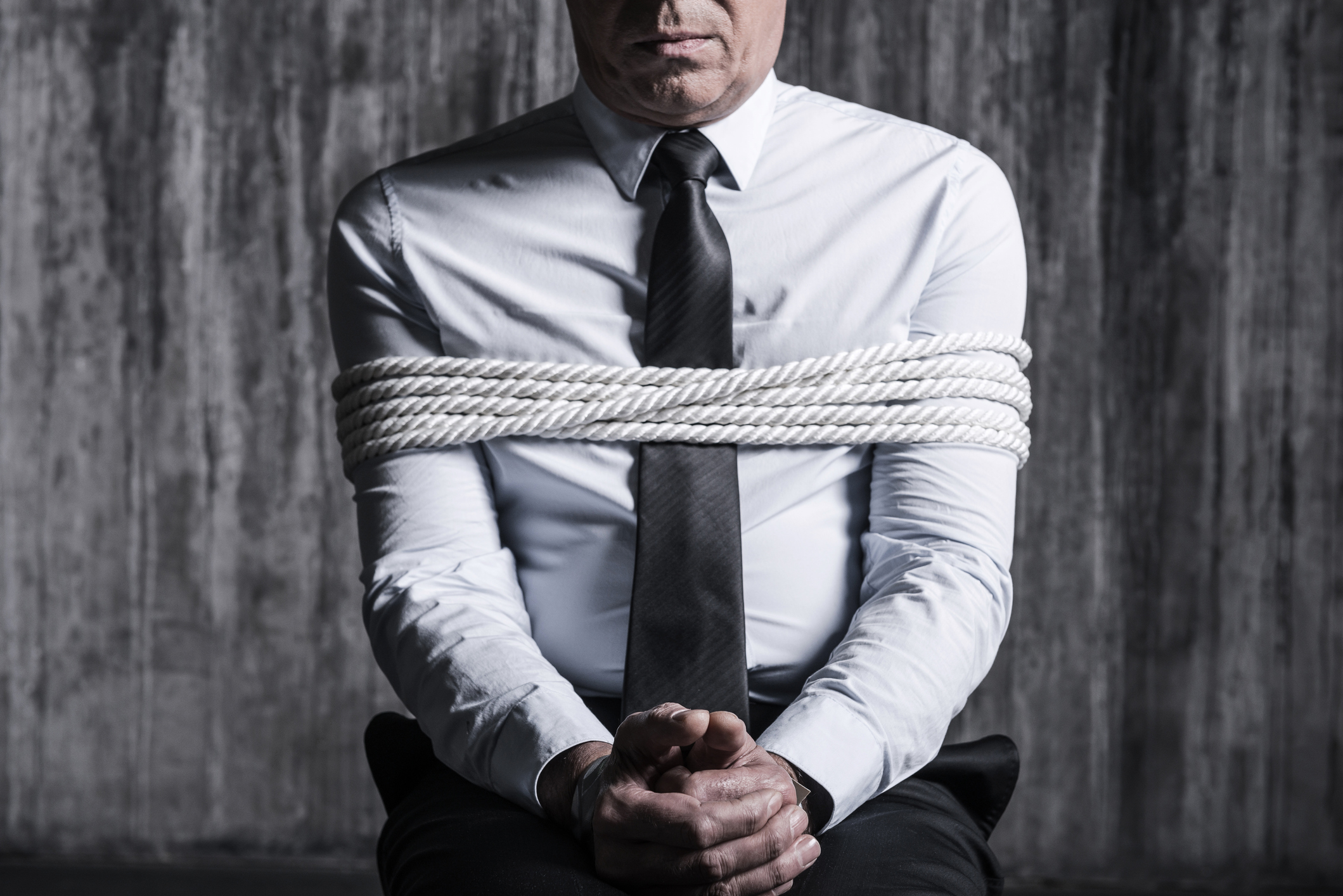 Cropped image of tied up businessman sitting at the chair with dirty wall  in the background