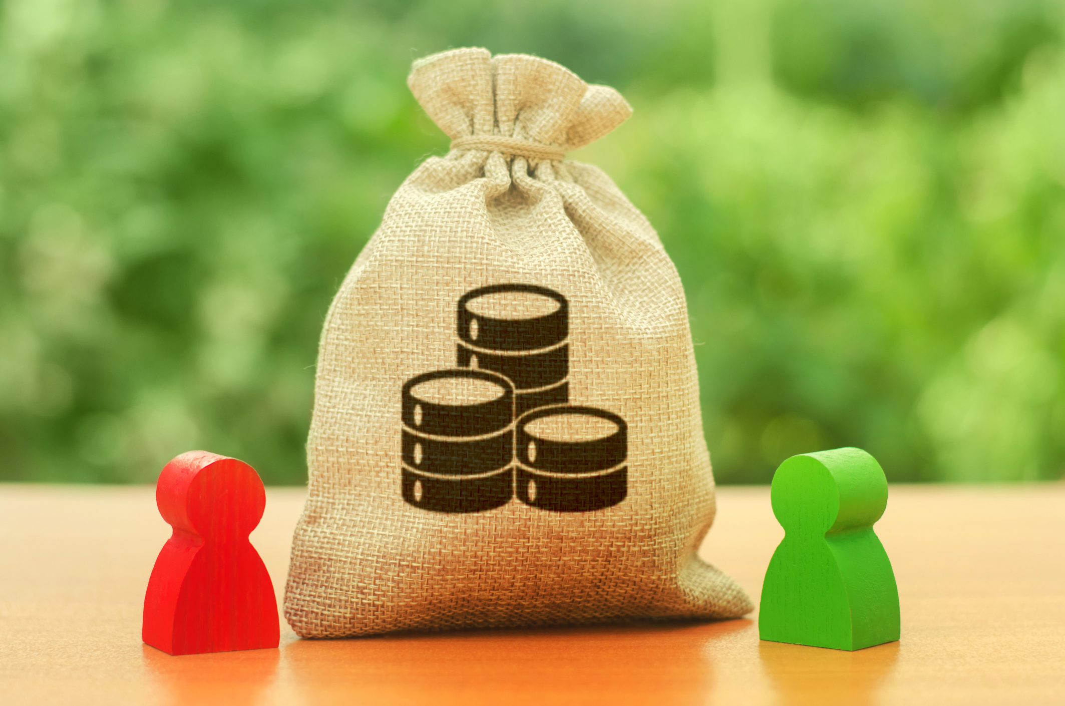 Money bag with money coins symbol and two people figures. Division of resources