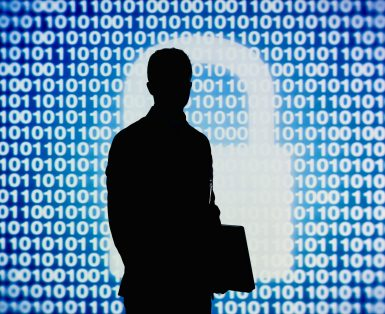 Man standing and holding laptop with code and white figure of a padlock behind him
