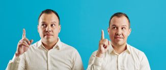 Young adult Caucasian twins wearing white shirts having idea, blue wall background