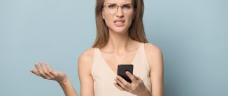 Frustrated young woman in glasses isolated on blue studio background hold smartphone