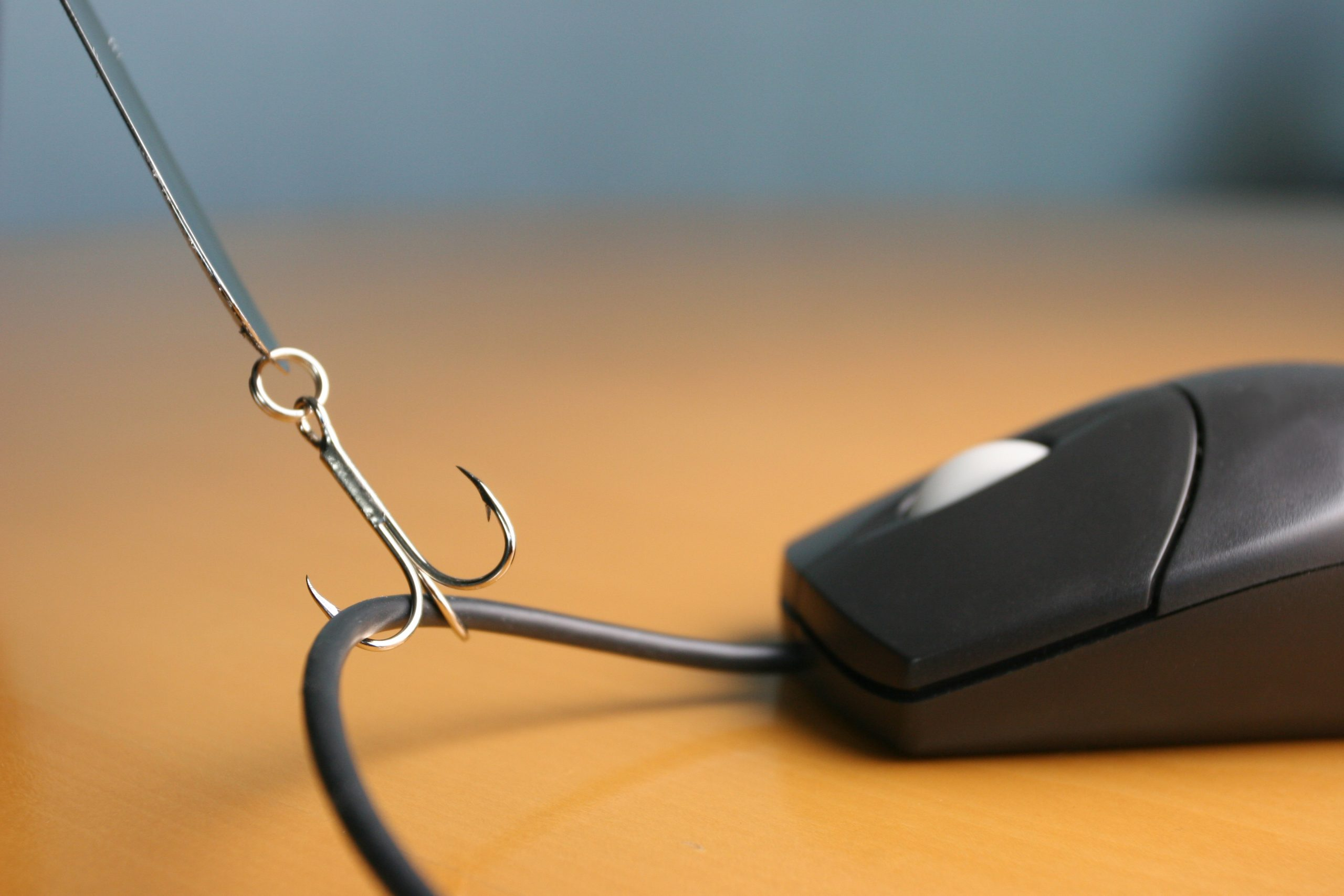 Close up of fishing hook snagging a computer mouse cord on a desktop.